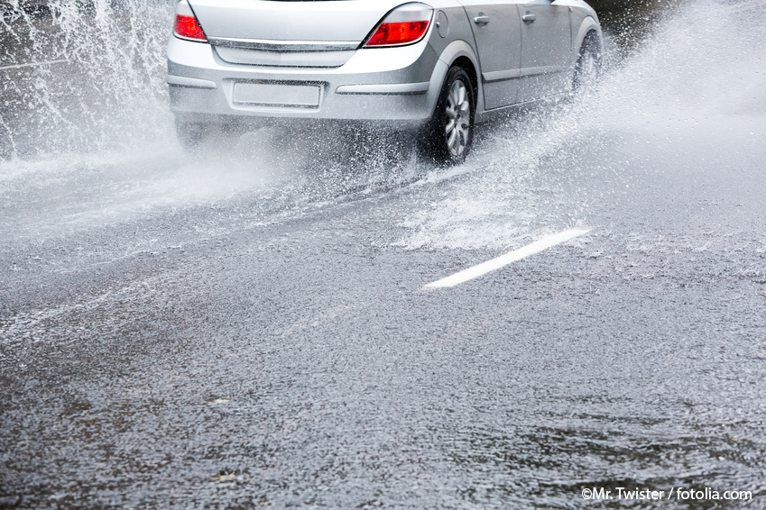 Road flooded with water on which driving silver gray car creates splashing water