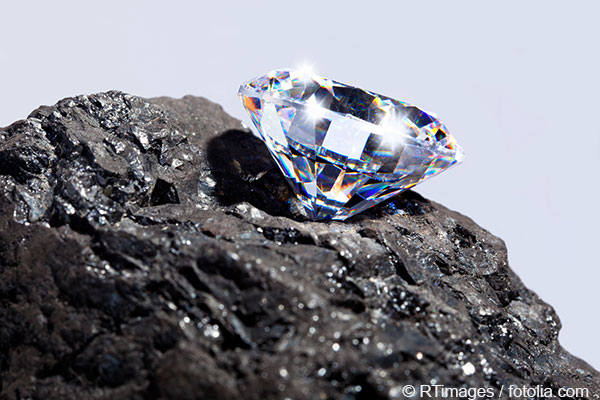 Close up of a sparkling cut diamond positioned on a dark stone