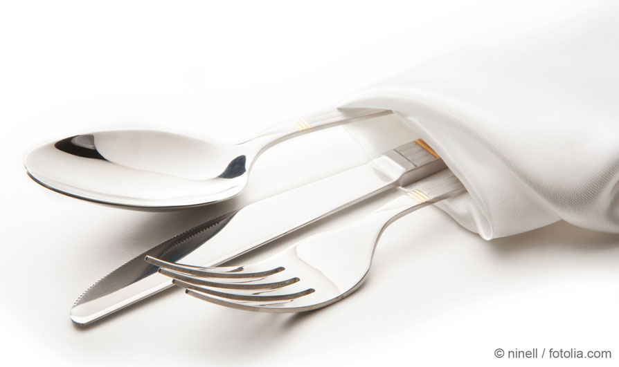 Cutlery set consisting of knife, fork and spoon wrapped in a napkin as an application example for silver